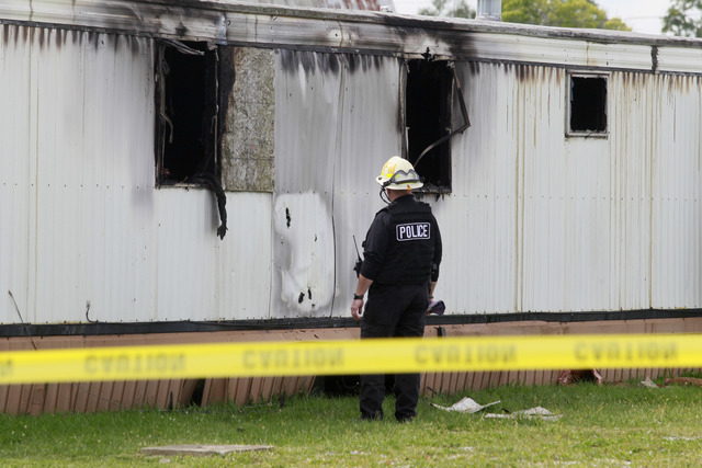 Wm. Timothy Spradlin, with the Division of the State Fire Marshal, investigates into the scene of a fire that killed five children and one adult on Sunday,  Sept. 15, 2013, in Tiffin, Ohio. The fi ...
