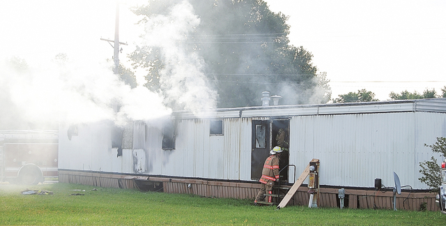 Firefighters extinguish a mobile home fire Sunday, Sept. 15, 2013, that killed a man and five children in Tiffin, Ohio, according to police. Fire crews pulled the man and the children from the hom ...