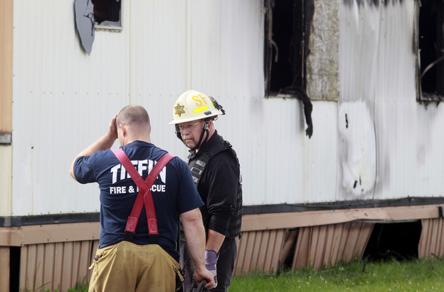 Wm. Timothy Spradlin, chief of the Fire and Explosion Investigation Bureau, right, speaks with a member of the Tiffin Fire and Rescue, left, during the investigation into the scene of a fire that  ...