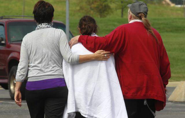 Anna Angel, center, is escorted to the car by Tress Hodkins, left, and Pat Boes, right, while exiting Tiffin Mercy Hospital on Sunday, Sept. 15, 2103 in Tiffin, Ohio. Angle is the mother to the th ...