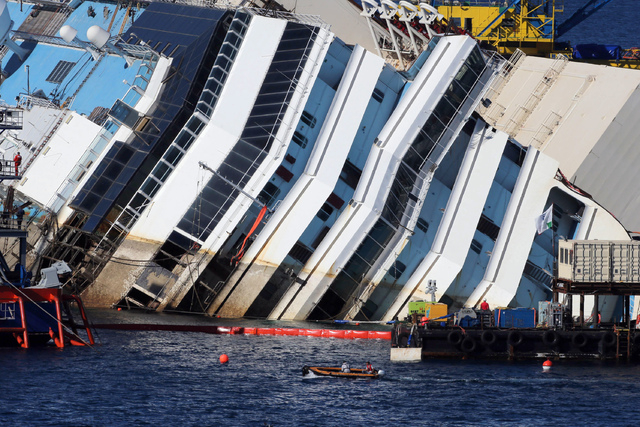The Costa Concordia ship lies on its side on the Tuscan Island of Giglio, Italy, Monday, Sept. 16, 2013. Engineers on Monday succeeded in wresting the hull of the shipwrecked Costa Concordia from  ...