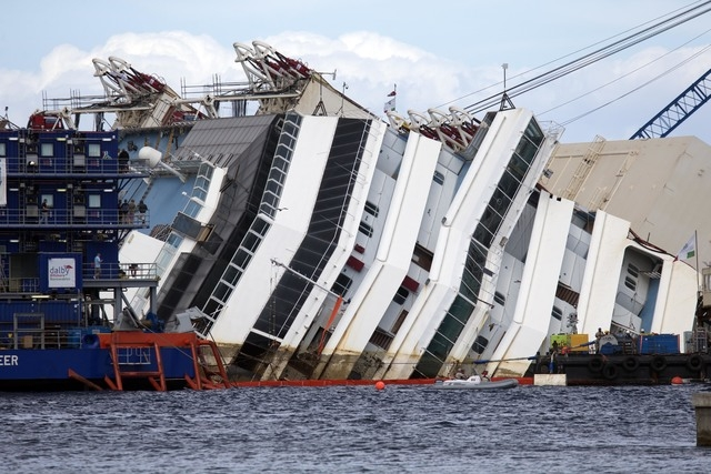 The Costa Concordia ship lies on its side on the Tuscan Island of Giglio, Italy, Monday, Sept. 16, 2013. An international team of engineers is trying a never-before attempted strategy to set uprig ...
