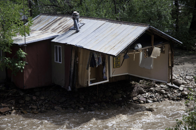 ADDS MAGS OUT-This photo taken on Friday, Sept. 13, 2013, shows the foundation of a house being undercut  in Lyons, Colo.  Access to the small mountain town was cut off after bridges were destroye ...