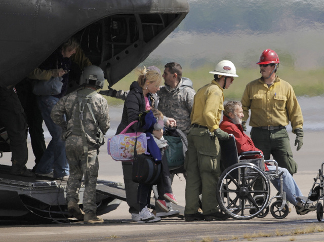 Flood victims are helped off of military helicopters at the Boulder Municipal Airport in Boulder, Colo., on on Monday,  Sept. 16,  2013, after being rescued. Thousands of people remained stranded  ...