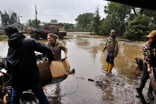 Local residents, left to right, Levi Wolfe, Miranda Woodard, Tyler Sadar, and Genevieve Marquez help salvage and clean property in an area inundated after days of flooding, in Hygeine, Colo., Mond ...