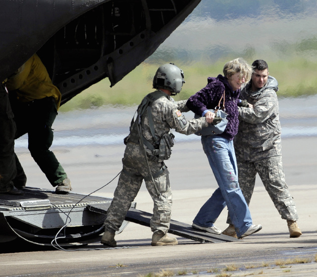 A woman is  helped off of a military helicopter at the Boulder Municipal Airport in Boulder, Colo., on on Monday,  Sept. 16,  2013, after being rescued. Thousands of people remained stranded by hi ...