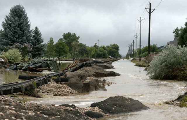 A truck rests next to the washed out railroad track in the Champion Greens neighborhood in Longmont,  Colo., Sunday Sept. 15, 2013.  Evacuations are underway Sunday morning in some Longmont neighb ...