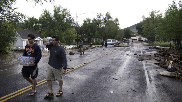 ADDS MAGS OUT- This photo taken on Friday, Sept. 13, 2013, shows two men carrying bottled water down a street in Lyons, Colo.  Access to the small mountain town was cut off after bridges were dest ...