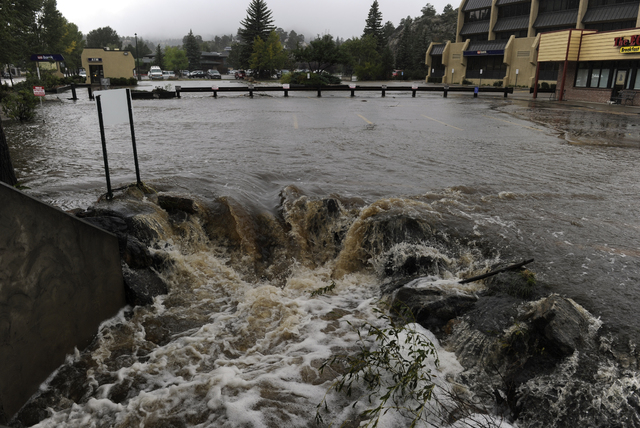 A heavy flow of water pours out of a parking lot on E. Elkhorn Ave. overwhelming a culvert heading under the roadway.  As a steady rain continues to fall, the town of Estes Park, Colo., begins Sun ...