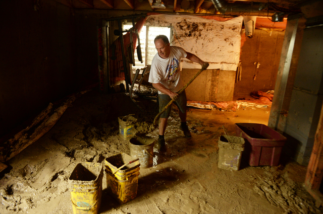 Mike Steinpach moves mud out from the basement of Stan McDonald's house damaged by flooding near the corner of Widgeon Dr. and Allen Drive. Longmont, Colo., Sunday Sept. 15, 2013. (AP Photo/ The D ...