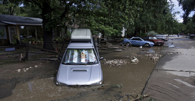 ADDS MAGS OUT-This photo taken on Friday, Sept. 13, 2013, shows vehicles damages by flood waters on a street in Lyons, Colo.  Access to the small mountain town was cut off after bridges were destr ...