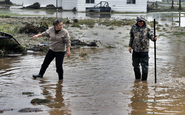 Miranda Woodard, left, and  Joey Schendel help salvage and clean property in an area inundated after days of flooding, in Hygiene, Colo., Monday Sept. 16, 2013.  Colorado mountain towns cut off fo ...