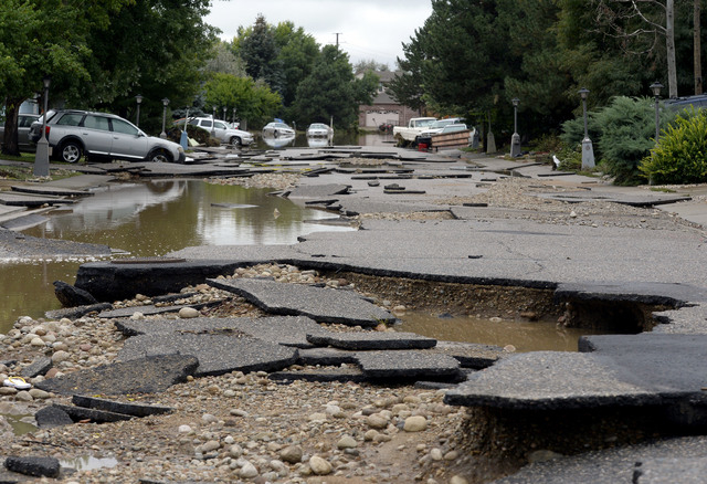 Hayden Court collapsed during the flooding of the Troxell neighborhood in Longmont,  Colo., Sunday Sept. 15, 2013.  Evacuations are underway Sunday morning in some Longmont neighborhoods because t ...