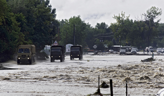 ADDS MAGS OUT-This photo taken on Friday, Sept. 13, 2013, shows National Guard trucks making their way down one of the main streets in Lyons, Colo.  Access to the small mountain town was cut off a ...