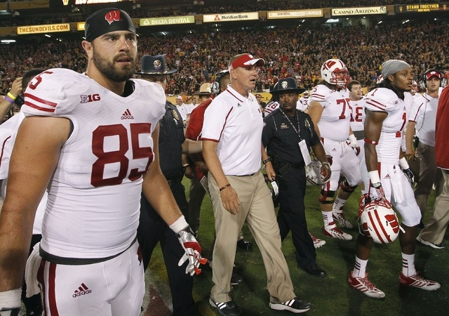 Wisconsin head coach Gary Andersen, middle, Brian Wozniak (85) and other Wisconsin players walk off the field in disbelief after a loss to Arizona State in an NCAA college football game on Saturda ...