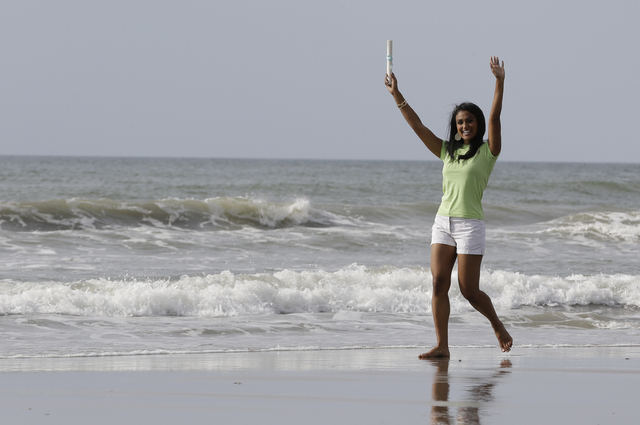 Miss America 2014 Nina Davuluri walks on the beach during the traditional dipping of the toes in the Atlantic Ocean the morning after being crowned Miss America, Monday, Sept. 16, 2013, in Atlanti ...