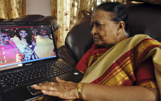 89-year-old Vege Koteshwaramma, looks at the photograph of her granddaughter Nina Davuluri, the first contestant of Indian origin to become Miss America, center on laptop screen, in Vijaywada, 280 ...