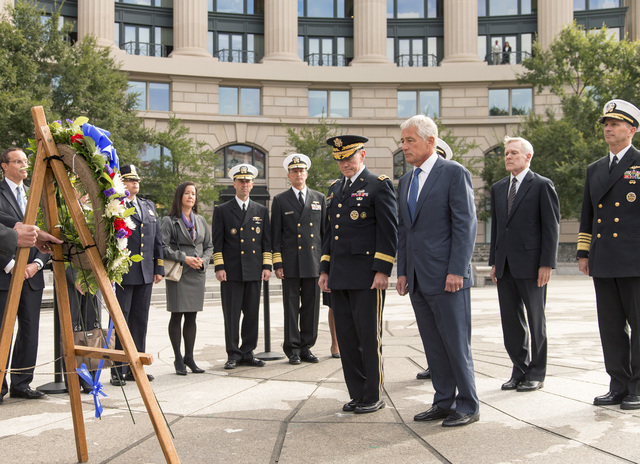 Defense Secretary Chuck Hagel, center right, and Joint Chiefs Chairman Gen. Martin Dempsey lead a delegation Tuesday at the Navy Memorial in Washington to remember the victims of Monday's deadly s ...