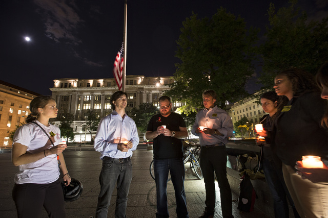 A small group holds a candle light vigil on Freedom Plaza to remember the victims of the shooting at the Washington Navy Yard Monday in Washington.  (AP Photo/J. Scott Applewhite)