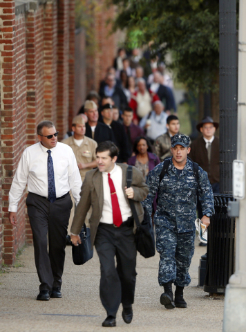 Military personnel and workers walk along the perimeter of the Washington Navy Yard Thursday. The Washington Navy Yard began returning to nearly normal operations three days after it was the scene ...