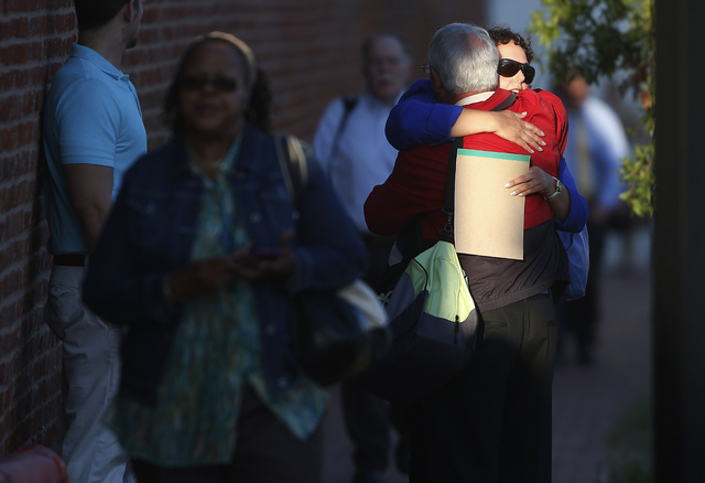 An unidentified woman hugs a man before entering the Washington Navy Yard as people returned to work on Thursday. (AP Photo/Charles Dharapak)