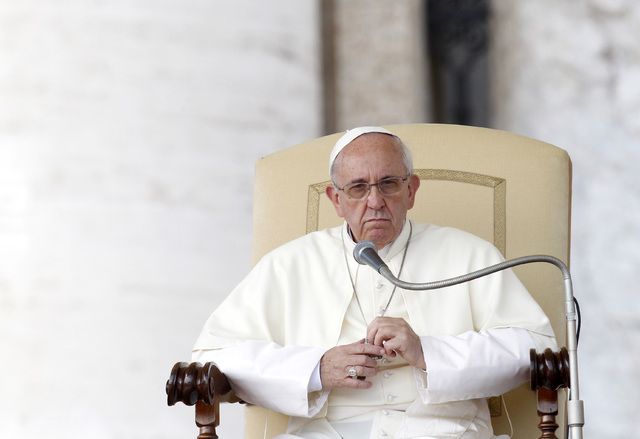 Pope Francis looks on during his weekly general audience in St. Peter's Square at the Vatican on Wednesday. The pontiff has warned that the Catholic Church's moral structure might fall if it doe ...