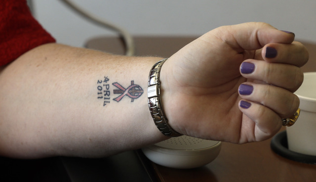 This Thursday, Sept. 5, 2013 photo shows Tracy Smith's tattoo marking her life-changing experience with cancer, during a visit Duke Cancer Center in Durham, N.C. Smith was treated at Duke in 2011  ...