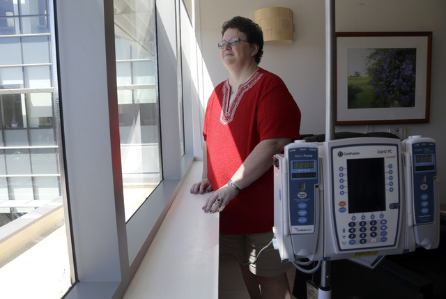 In this Thursday, Sept. 5, 2013 photo, Tracy Smith looks out of a window at the infusion center at Duke Cancer Center in Durham, N.C. Smith was treated at Duke in 2011 for breast cancer that had s ...