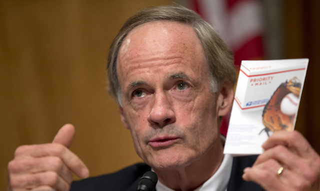 Committee Chairman Sen. Thomas Carper, D-Del., holds up a Priority Mail flyer during the Senate Homeland Security and Governmental Affairs Committee hearing on Capitol Hill, Thursday, Sept. 19, 20 ...