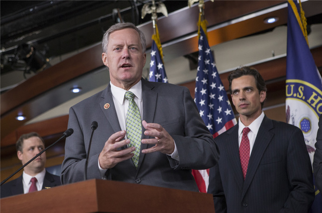 Rep. Mark Meadows, R-N.C, center, Rep. Tom Graves, R-Ga., right, and other conservative Republicans discuss their goal of obstructing the Affordable Care Act, popularly known as Obamacare, as part ...