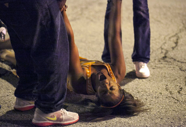 In this Thursday, Sept. 19, 2013, photo, a women becomes emotional near the scene of a shooting at Cornell Square Park in Chicago's Back of the Yard neighborhood that left multiple victims includi ...