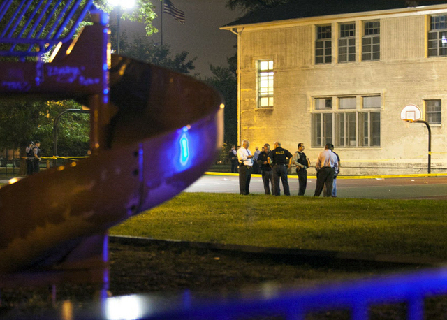 In this Thursday, Sept. 19, 2013, photo, officials convene at the scene of a shooting at Cornell Square Park in Chicago's Back of the Yard neighborhood that left multiple victims including a 3-yea ...