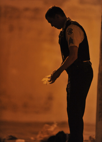 A Chicago Police detective investigates the scene where 11 people, including a 3-year-old child, were shot in a city park on the south side of Chicago, Thursday, Sept. 19, 2013. Authorities said n ...