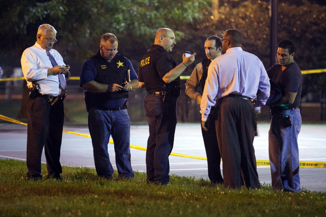 In this Thursday, Sept. 19, 2013, photo, officials convene near the scene of a shooting at Cornell Square Park in Chicago's Back of the Yard neighborhood that left multiple victims including a 3-y ...