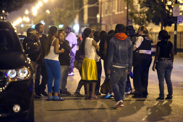 In this Thursday, Sept. 19, 2013, photo, bystanders convene near the scene of a shooting at Cornell Square Park in Chicago's Back of the Yard neighborhood that left multiple victims including a 3- ...