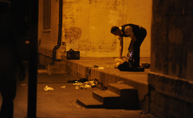 A Chicago police officer picks through debris at the crime scene where a number of people were shot, including a 3-year-old child, in a city park on the south side of Chicago, Thursday, Sept. 19,  ...