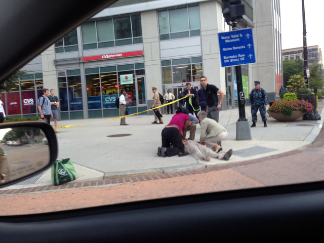 In this photo, which The AP obtained from Don Andres, shooting victim Vishnu Pandit is assisted on the sidewalk while awaiting the arrival of emergency medical personnel after coworkers took him b ...