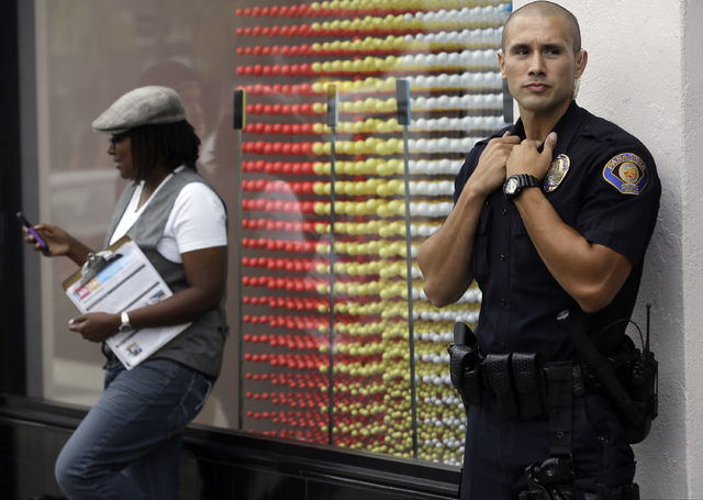 Pasadena Police officer M. Chavarin guards the front of the Apple store in Pasadena, Calif., as customers wait in line for the latest versions of the iPhone during the opening day of sales of the  ...