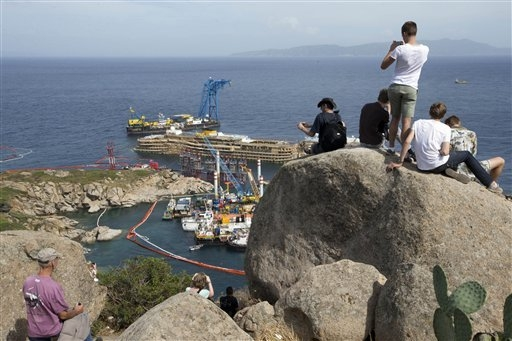 In this photo taken on Monday, Sept. 16, 2013 people take pictures of the Costa Concordia ship, on the Tuscan Island of Giglio, Italy, Wednesday, Sept. 18, 2013. For more than a year, tourists flo ...