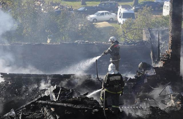 Firefighters work amidst the debris of a psychiatric hospital destroyed by fire in the Novgorod region town of Luka September 13, 2013. The fire raged through the Russian psychiatric hospital on F ...