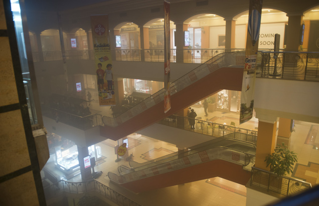 Armed police take cover behind escalators as smoke fills the air inside the Westgate Mall in Nairobi, Kenya Saturday, Sept. 21, 2013. Gunmen threw grenades and opened fire Saturday, killing at lea ...