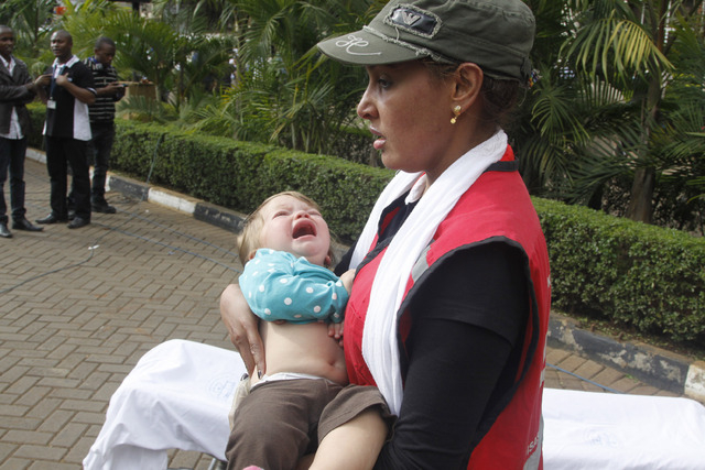 A Red Cross assistant helps a child outside the Westgate Mall in Nairobi, Kenya Saturday, Sept. 21, 2013, after gunmen threw grenades and opened fire during an attack that left multiple dead and d ...