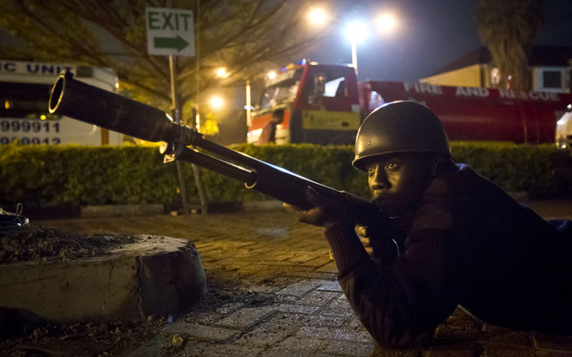 An armed police officer takes cover during a bout of gunfire outside the Westgate Mall in Nairobi, Kenya Saturday, Sept. 21, 2013.  Gunmen threw grenades and opened fire Saturday killing at least  ...