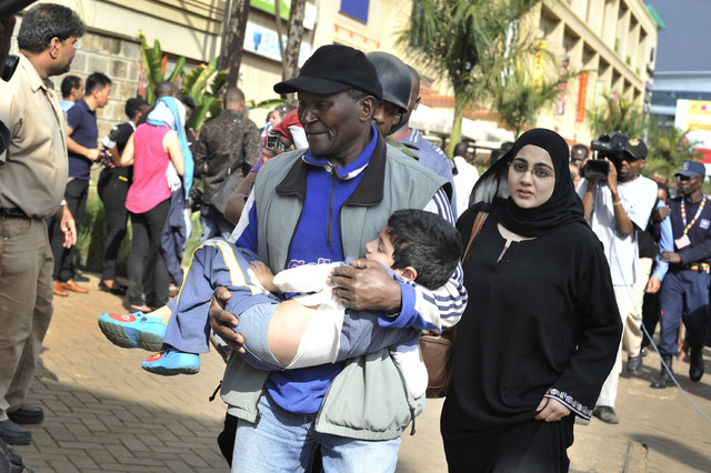 A rescue worker helps a child outside the Westgate Mall in Nairobi, Kenya Saturday, Sept. 21, 2013, after gunmen threw grenades and opened fire during an attack that left multiple dead and dozens  ...