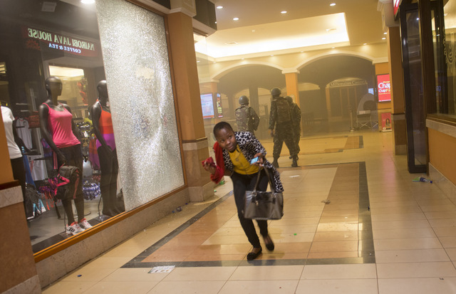 A woman who had been hiding during the gun battle runs for cover after armed police, seen behind, enter the Westgate Mall in Nairobi, Kenya, Saturday, Sept. 21, 2013. Gunmen threw grenades and ope ...
