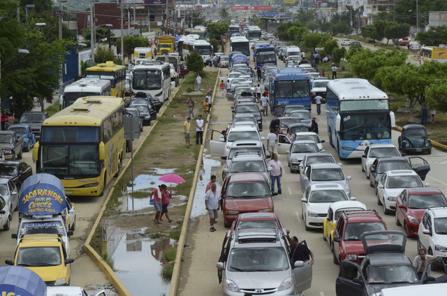 People that were stranded when Tropical Storm Manuel hit wait for the highway to open in the Pacific resort city of Acapulco, Mexico, Friday, Sept. 20, 2013. The country's Transportation Departmen ...