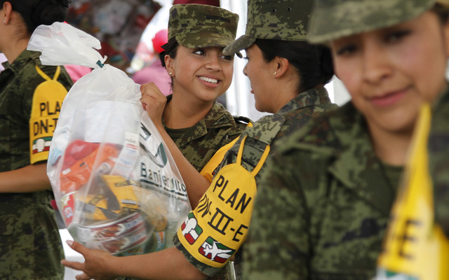Soldiers load humanitarian aid bound for storm victims of Tropical Storm Manuel, in the Zocalo, Mexico City's main plaza, Friday, Sept. 20, 2013. Federal police and soldiers have been helping move ...