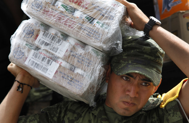 A soldier carries cartons of canned vegeatables to a waiting vehicle as part of the humanitarian aid bound for storm victims of Tropical Storm Manuel, in the Zocalo, Mexico City's main plaza, Frid ...