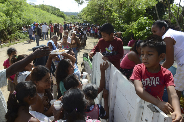 Villagers affected from the rains and floods caused by Tropical Storm Manuel line up to get a simple meal donated by residents of a nearby community in the village of Salsipuedes, Mexico, Friday,  ...