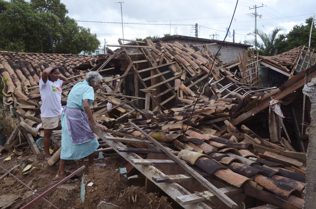Two women try to salvage what was left of their home after it was destroyed by the rains and floods caused by Tropical Storm Manuel in the village of Salsipuedes, Mexico, Friday, Sept. 20, 2013. M ...